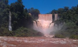 Magnificent Iguazu waterfalls with red brown water royalty free stock photo