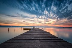 Magnificent lake sunset. Magnificent long exposure lake sunset with boats and a wooden pier royalty free stock images