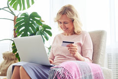 Magnificent madam holding credit card while working in laptop Stock Images