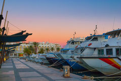 Magnificent magenta sunset color in marina harbor. End of a warm sunny day in Ibiza, St Antoni de Portmany, Spain. Boats in for the evening in marina harbor stock image
