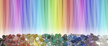 Magnificent Multicoloured Chakra Healing Stones header. Wide rainbow coloured graduated banner copy space above with crystal healer`s row of chakra coloured Stock Photos
