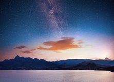 Magnificent panorama of sunrise over the sea. Vibrant night sky with stars and nebula and galaxy. Deep sky astrophoto. Magnificent panorama over the sea. Vibrant royalty free stock photo
