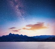Magnificent panorama of sunrise over the sea. Vibrant night sky with stars and nebula and galaxy. Deep sky astrophoto. Magnificent panorama over the sea. Vibrant royalty free stock photography