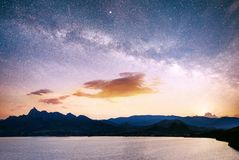 Magnificent panorama of sunrise over the sea. Vibrant night sky with stars and nebula and galaxy. Deep sky astrophoto. Magnificent panorama over the sea. Vibrant stock photos