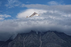 A magnificent peak in the Himalayas rising beyond the clouds. Royalty Free Stock Image