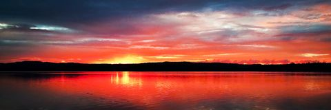 Magnificent red cloud coastal sunrise reflections. royalty free stock photos