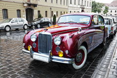 The magnificent retrocar the Jaguar to stand on the ancient street of Budapest Royalty Free Stock Photography