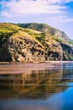 Magnificent rock formations reflected in gentle tidal waves running over the shore. stock photos
