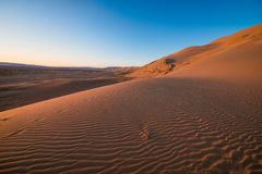 Magnificent sandy waves on dunes in desert. At hot and windy morning Royalty Free Stock Image