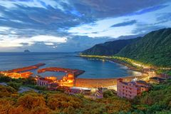 Magnificent scenery of a fishing village and a coastal highway along beautiful coastline before sunrise Stock Photography