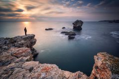 Sea sunrise at rocky beach stock photos