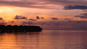 Magnificent sea sunset. Silhouettes of sea bungalow on the background of orange sky merging into the sea Stock Photo