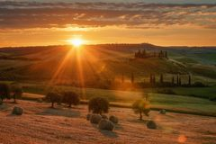 Magnificent spring landscape at sunrise.Beautiful view of typical tuscan farm house, green wave hills. Stock Photography