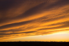 Magnificent Sunset and Cloud Formations. A thick blanket of cloud provides a beautiful contoured canvas for the golden yellow sunset in Montana Stock Photography