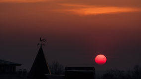 Magnificent sunset over the rooftops. wind indicator. Royalty Free Stock Images