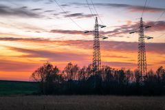 Magnificent sunset over two electricity pylons Royalty Free Stock Photo