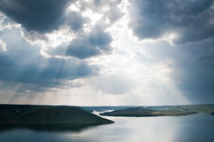 Magnificent view of the river. Rays of sun shining through the clouds. The river runs into the distance. The river is calm. The sky is cloudy Royalty Free Stock Image