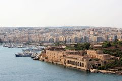 Magnificent view of several cities on the coast of the island of Malta. The medieval fortifications of yellow stone, a large calm bay with numerous ships and royalty free stock photo