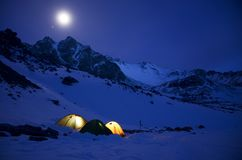 Magnificent view of the snow-capped mountains in a moonlit night. Night view of Mount Munku-Sardyk. Munku-Sardyk in the light of the moon. Tent and Camping Stock Photo