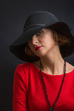 The magnificent young woman in a dark hat with wide fields and  bright scarlet dress. The magnificent young woman in a dark hat with wide fields and a bright Stock Image