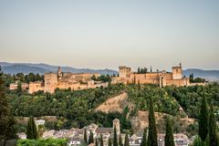 The magnificient Alhambra of Granada, Spain. Alhambra fortress a. T sunset viewed from Mirador de San Nicolas during evening twilight hour royalty free stock images