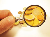 Magnified coins. A hand holds a small magnifier, using it to magnify the gold Euro coins royalty free stock images