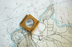 A magnified view of map. An old magnifier lens lying on a map Royalty Free Stock Photos