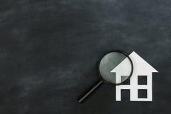 Magnifier που ψάχνει το σπίτι που απομονώνεται στον πίνακα κιμωλίας στοκ εικόνα με δικαίωμα ελεύθερης χρήσης
