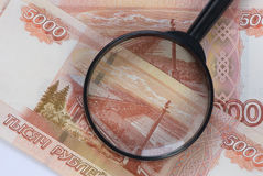 Magnifier on banknotes Royalty Free Stock Images