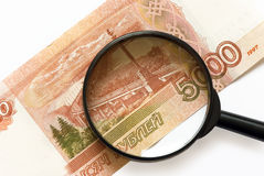 Magnifier on banknotes Stock Images