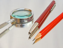 Magnifier, biro and pencil. Royalty Free Stock Photography