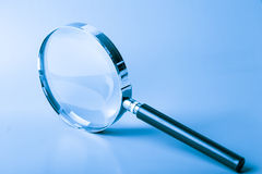 Magnifier on blue Royalty Free Stock Image