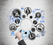 Magnifier with business icons. Hand holding magnifier with business icons Stock Photo