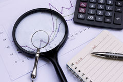 Magnifier, calculator, pen, notebook and financial chart, busine Stock Images