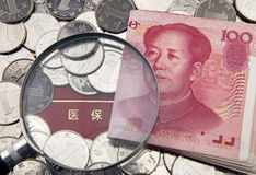 A magnifier with china yuan on the background of medical insurance bankbook Stock Photos