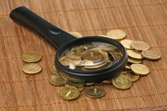 Magnifier and coins Royalty Free Stock Image