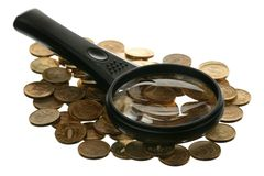 Magnifier and coins Stock Image