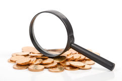 Magnifier and coins Stock Photos
