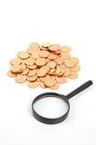 Magnifier and coins Royalty Free Stock Images