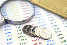 Magnifier and coins on data sheet Stock Images
