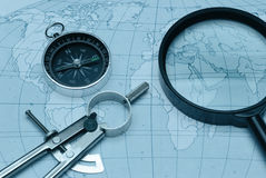 Magnifier , compass and map Stock Photos