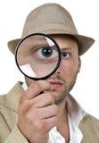 Magnifier da terra arrendada do homem perto do olho Fotografia de Stock Royalty Free