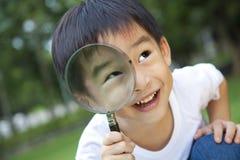 Magnifier da terra arrendada do menino imagem de stock
