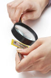 Magnifier della holding della mano che analizza un bollo Immagini Stock