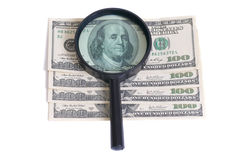 Magnifier with dollars Stock Images