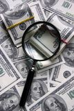 Magnifier and dollars Royalty Free Stock Image