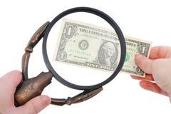 Magnifier e dólar nas mãos foto de stock