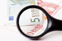 Magnifier e dinheiro imagem de stock