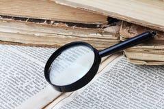 Magnifier e vecchi libri Fotografia Stock