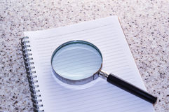 Magnifier with empty book on conceptual idea. Magnifier with empty book on the table Royalty Free Stock Photography
